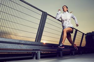 Athletic,Woman,Running,During,Sunset,On,Rooftop,Of,Parking,,Garage